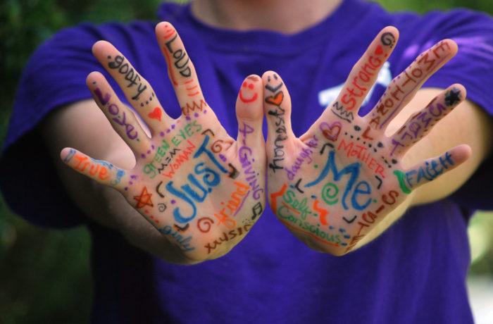Odwrócone wierzchnią częścią dłonie pokryte napisami określającymi to, kim jest osoba na zdjęciu