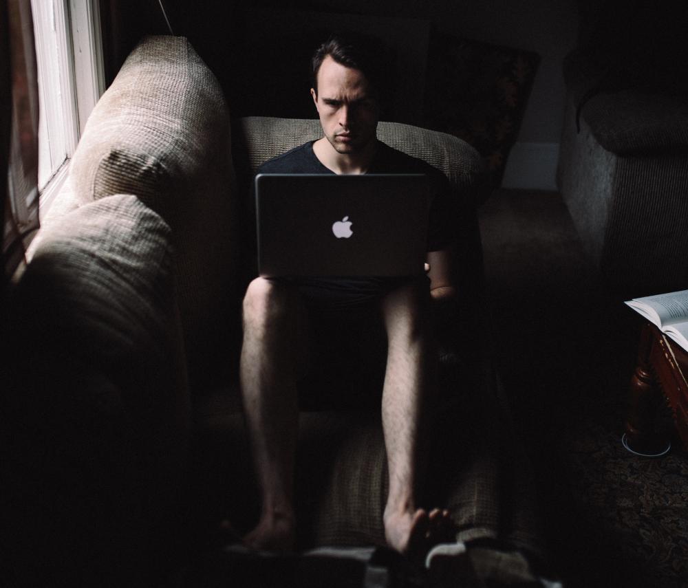 Mężczyzna z surową miną, siedzący przed komputerem